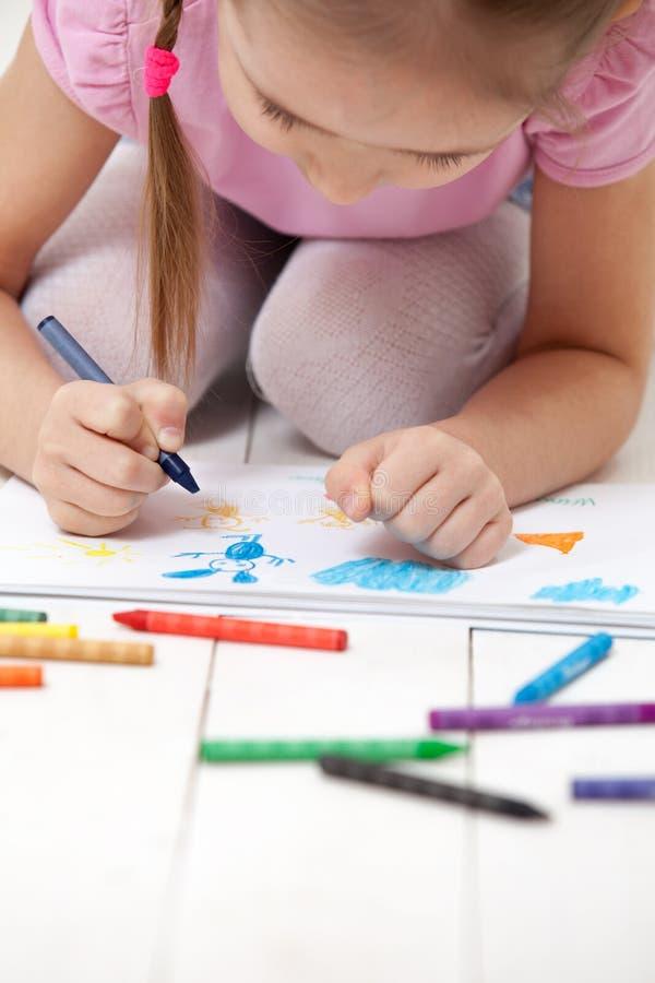 Flickan drar med färgpennor i albumet royaltyfri foto