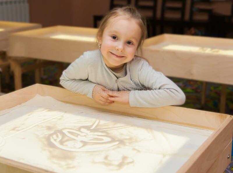 Flickan drar med sand på en ljus tabell arkivbild