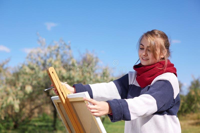 Flickan drar på en staffli mot en bakgrund av klar himmel arkivfoton