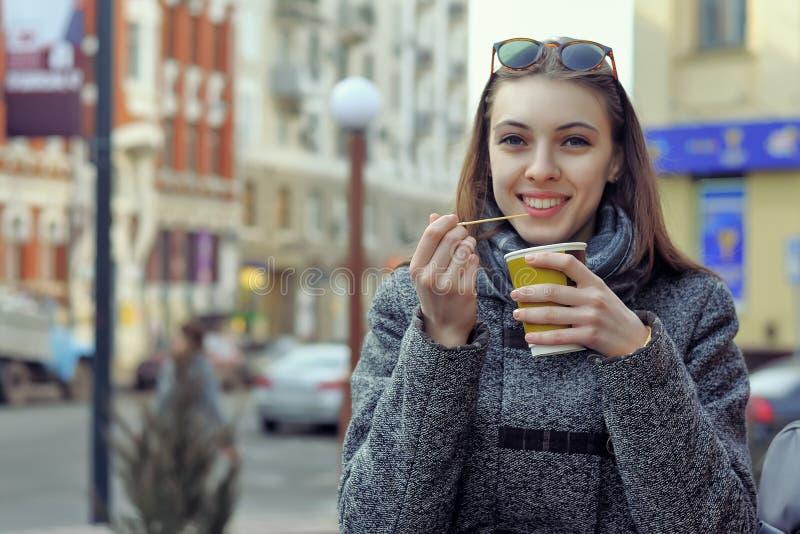 Flickan dricker en varm drink från en plast- kopp arkivbilder