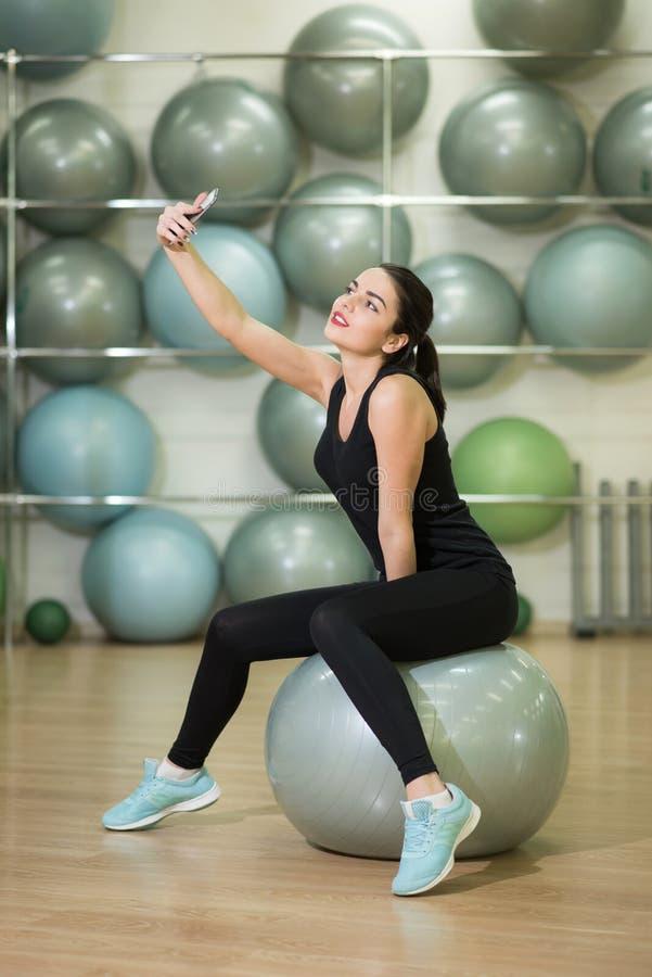 Flickan efter övningar med bollen gör selfie arkivbild
