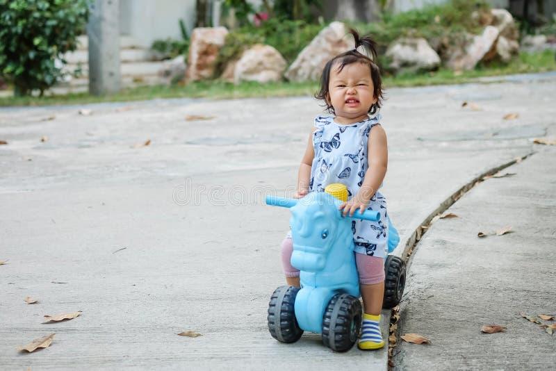 Flickan för closeupen rider lite en cykelleksak för unge med den lyckliga framsidan på cementgolv i parkerar texturerad bakgrund  arkivfoton