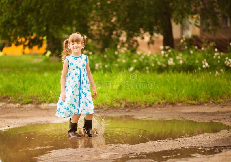 Flickan för den lilla ungen kör till och med en pöl Sommar fotografering för bildbyråer