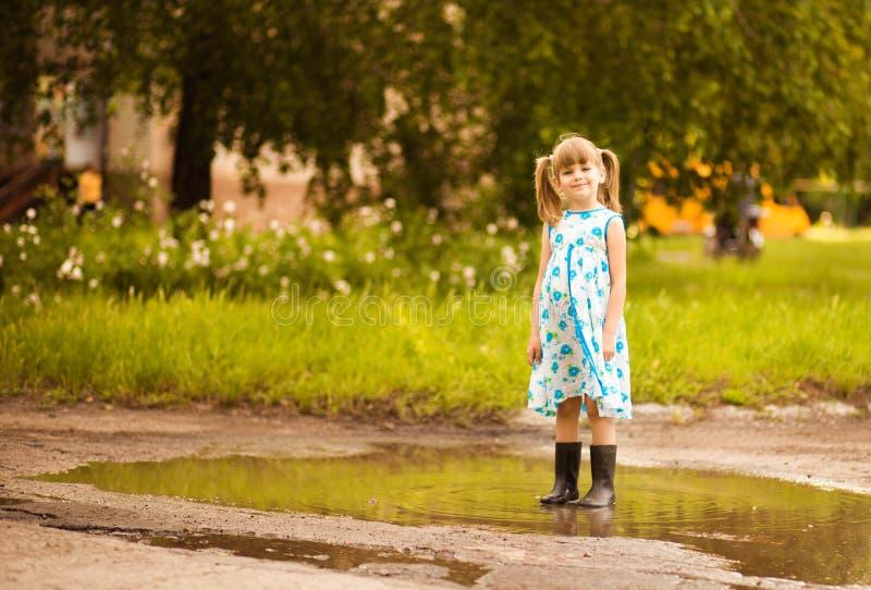 Flickan för den lilla ungen kör till och med en pöl Sommar royaltyfria foton