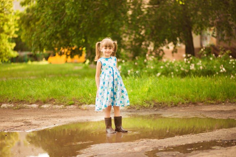 Flickan för den lilla ungen kör till och med en pöl Utomhus- sommar arkivbilder