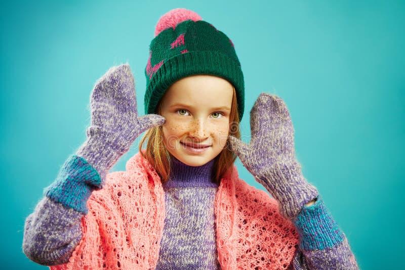 Flickan för det härliga barnet bär vintertumvanten, den varma tröjan, hatten med pompomen och den openwork uddehalsduken på isole royaltyfria foton