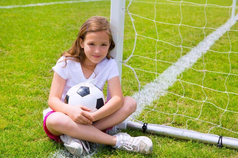 Flickan för fotbollfotbollungen kopplade av på gräs med bollen royaltyfria foton