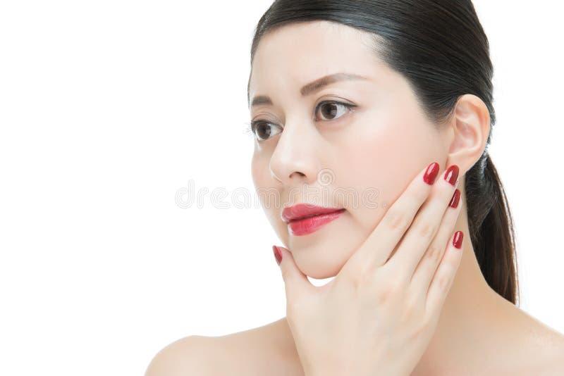 Flickan för läppstift för modeskönhet spikar den asiatiska röda med polermedelfingret royaltyfri foto
