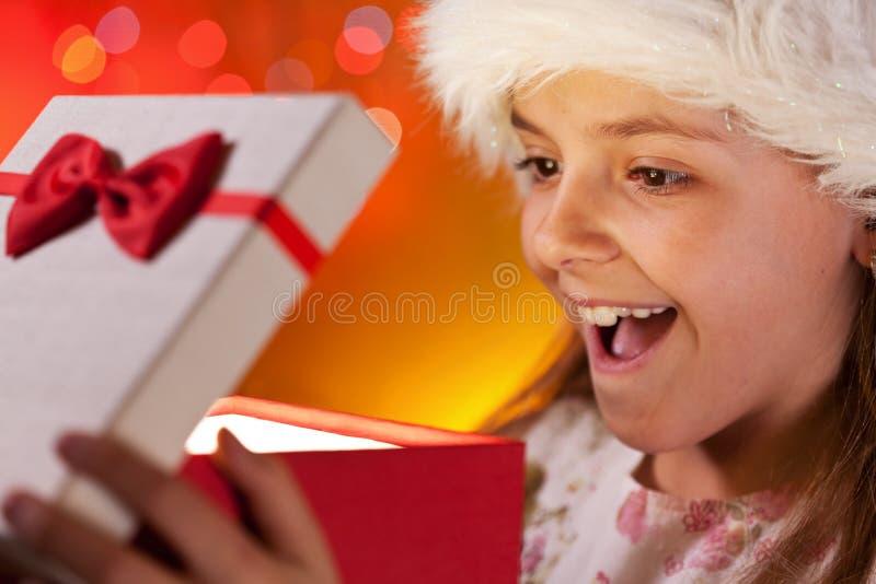 Flickan för lycklig jul som får gåvan önskade hon, på - closeupen royaltyfria foton