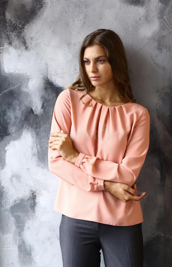 Flickan för modemodellen i grå färger klår upp på blå väggbakgrund arkivfoton