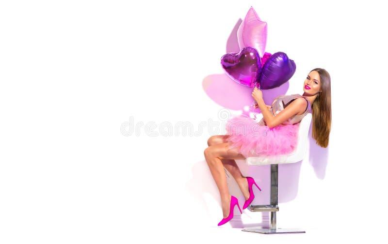 Flickan för partiet för skönhetmodemodellen med hjärta formade att posera för luftballonger som sitter på stol Födelsedagparti, v royaltyfria bilder