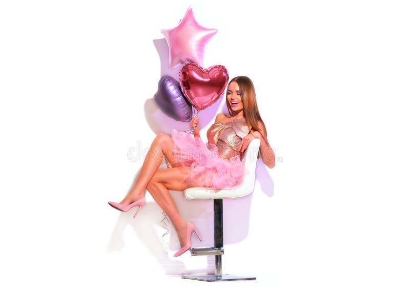 Flickan för partiet för skönhetmodemodellen med hjärta formade luftballonger som har gyckel som sitter på stol Härlig ung brunett royaltyfri bild