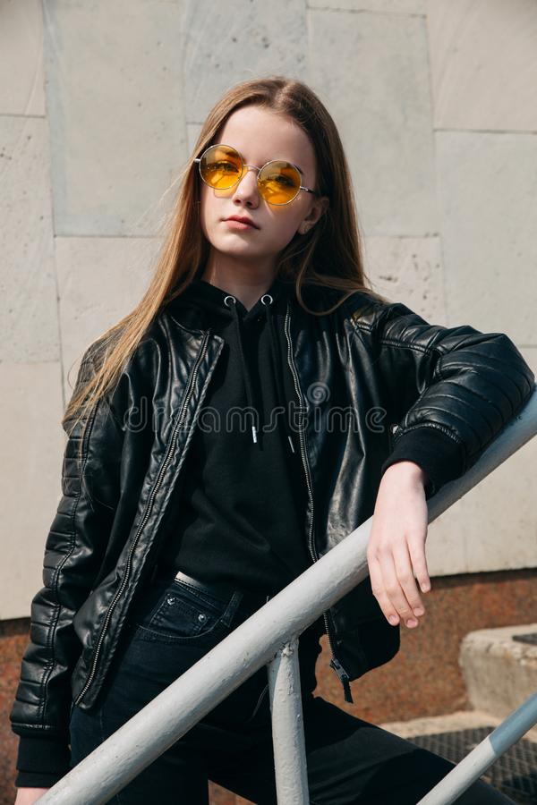 Flickan för tonåringen för modeståenden vaggar den nätta i solglasögon och svart stil över stadsbakgrund royaltyfri fotografi