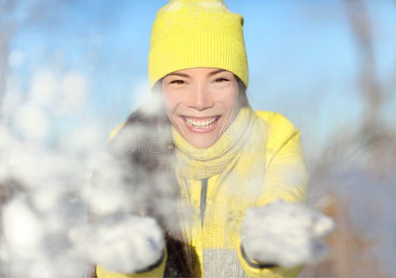 Flickan för vintersnökampen som spelar att kasta, kastar snöboll arkivbild