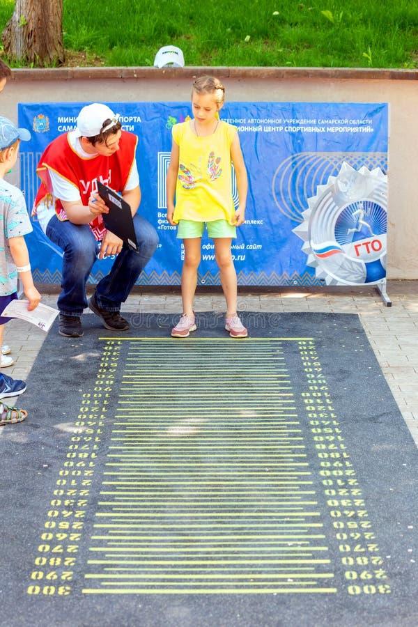Flickan förbereder sig att hoppa på längden för att sätta sportnormal arkivfoto