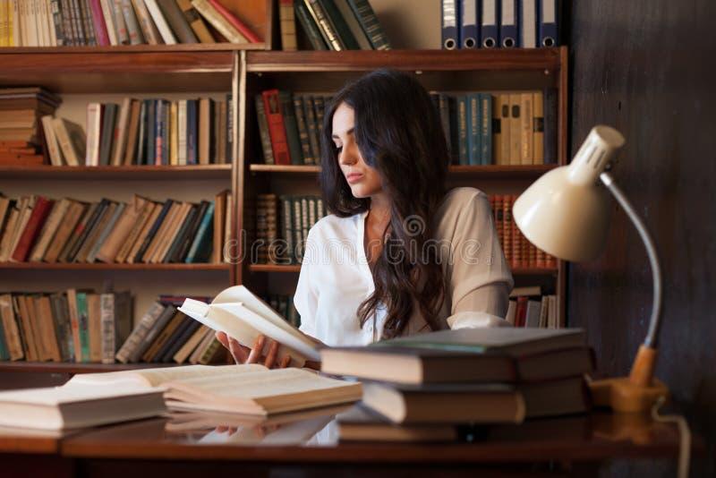 Flickan förbereder sig för examenläseboken på arkivet royaltyfri foto