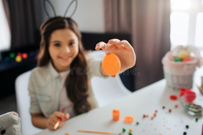 Flickan förbereder sig för påsk bara Hon sitter på tabellen i orange ägg för rum och för show på kamera Flickaleende Hon målar oc fotografering för bildbyråer