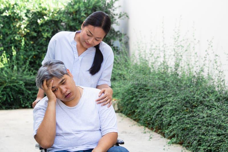 Flickan försöker att ta för att att bry sig en tålmodig man i en rullstol, honom har en huvudvärk De ?r par royaltyfri bild