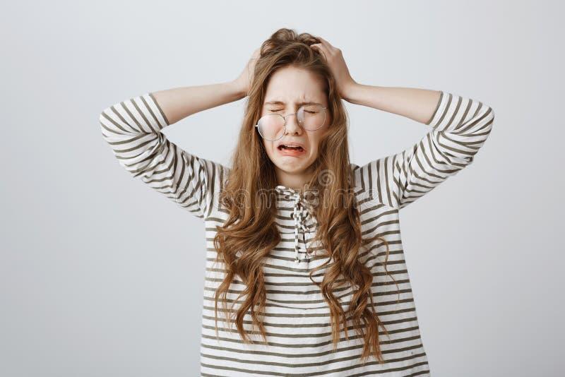 Flickan frågar för hjälp och att ha problem och huvudvärk från arbete Nätt gnällande kvinna med blont hår i genomskinligt royaltyfria foton
