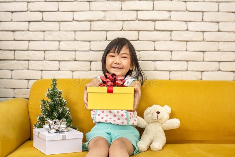 Flickan framlägger en julgåva flicka som visar gåvaasken Gullig asiatisk unge som rymmer en julask lyckligt nytt år glatt royaltyfria foton
