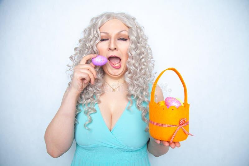 Flickan gäspar från leda på påsken blondinen rymmer en borrad korg med kulöra ägg och vit studiobakgrund royaltyfri fotografi