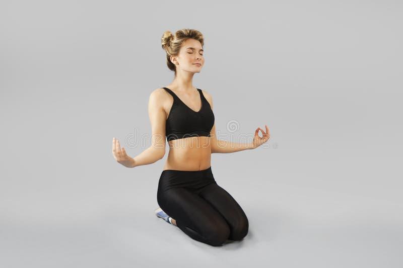Flickan går in för sportar på en isolerad bakgrund som gör olika övningar av gymnastik och kondition Begreppet av ett sunt royaltyfria bilder