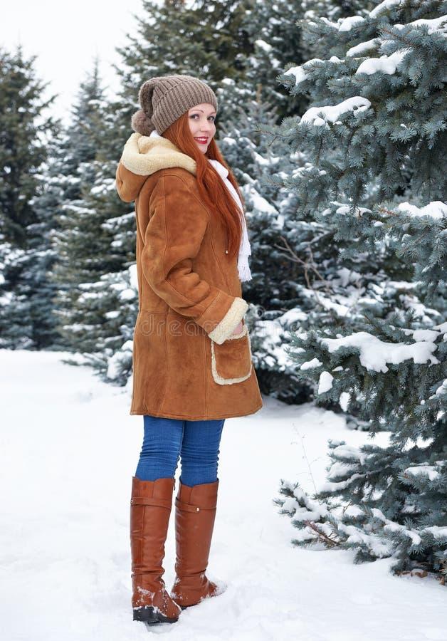 Flickan går i vinter parkerar på dagen Granträd med snö Full längd för rödhårig mankvinna arkivbild