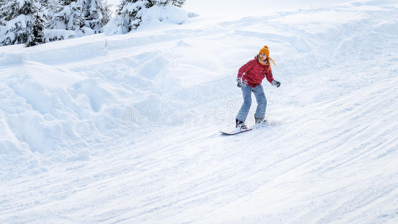 Flickan går på en snowboard på skidalutningarna royaltyfri fotografi
