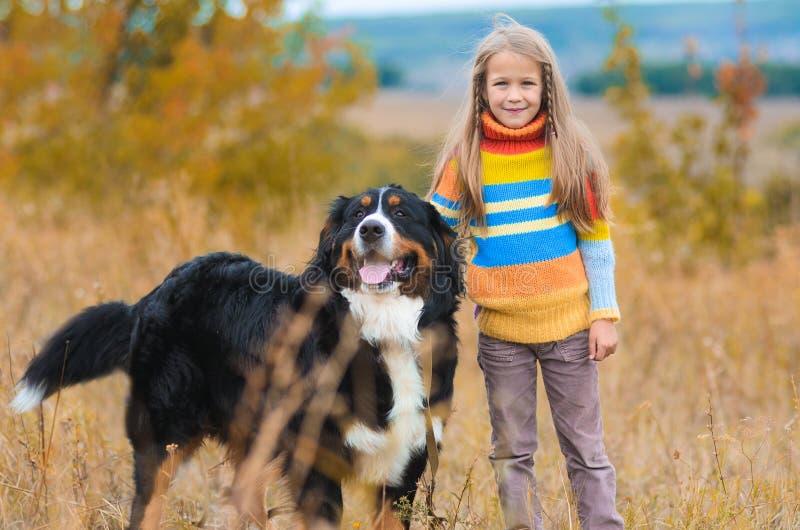 flickan går på med hennes fyrbenta vän på höstfält Berner royaltyfri bild