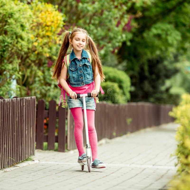 Flickan går till skolan på en sparkcykel royaltyfria foton