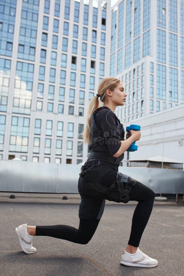 Flickan gör övningar med hantlar på den elektriska muskelstimulansmaskinen royaltyfri foto