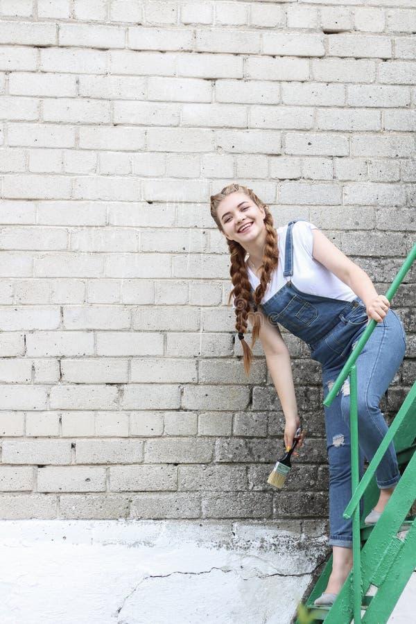 Flickan gör att förbereda sig för att måla en träyttersidagazebo, staket royaltyfria bilder