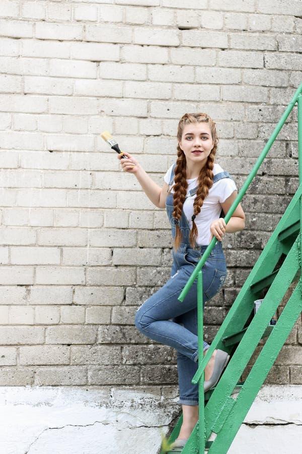 Flickan gör att förbereda sig för att måla en träyttersidagazebo, staket royaltyfria foton