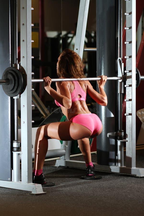 Flickan gör att knastra med vikt i idrottshall arkivfoton