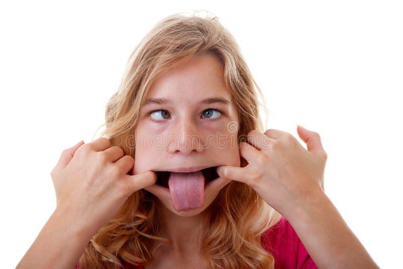 Flickan gör den roliga framsidan i closeup royaltyfria foton