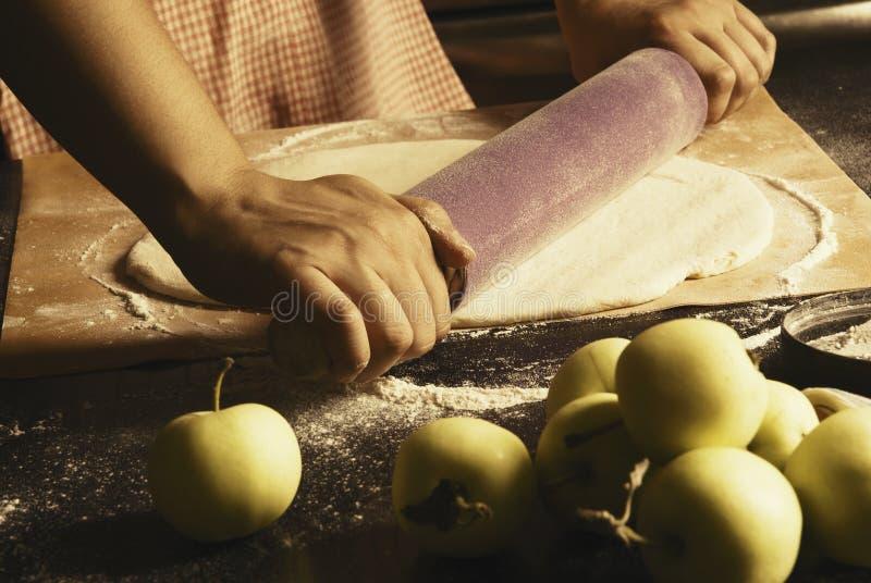 Flickan gör en äppelpaj royaltyfri bild
