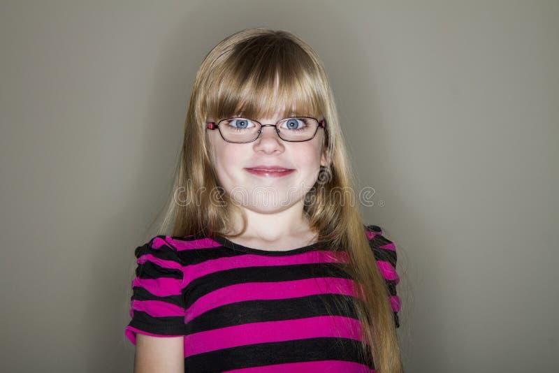 Flickan gör ett gulligt men roligt seende leende arkivbilder