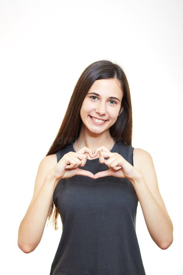 Flickan gör händerna av de isolerade bärande exponeringsglasen för hjärta på vit bakgrund arkivbilder