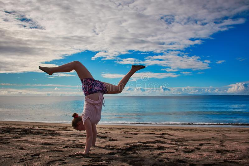 Flickan gör handstans på stranden arkivbild