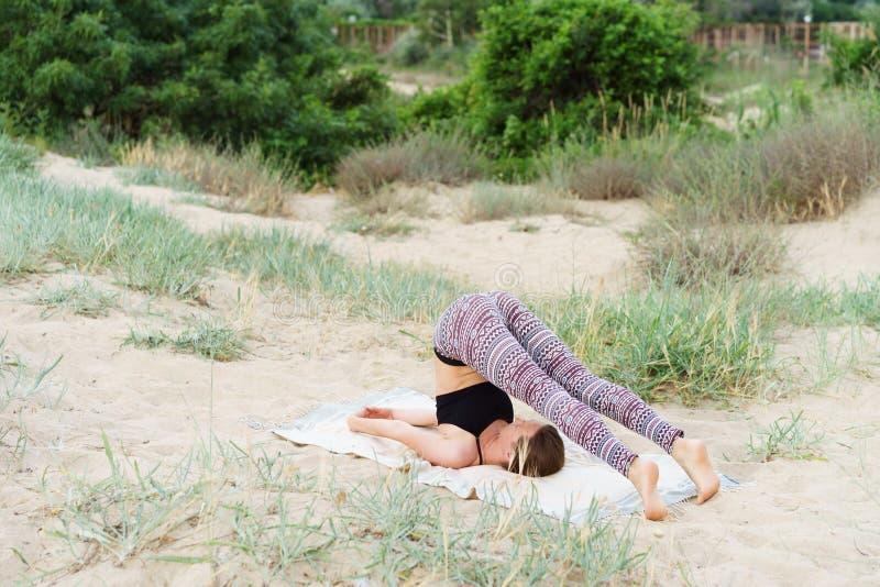 Flickan gör inverterade yogaasanas i det utomhus-, plogen poserar royaltyfri foto