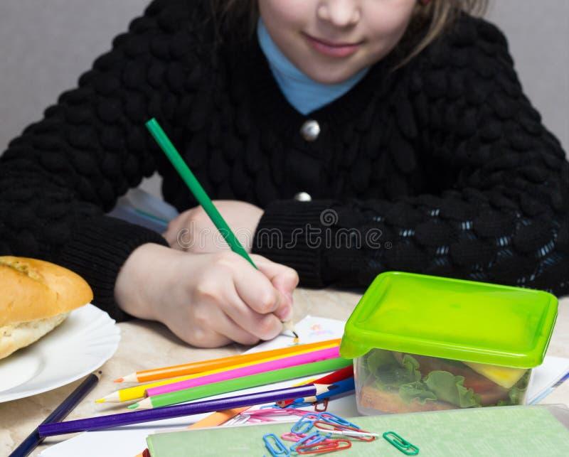 Flickan gör kurserna, på tabelllögnerna en smörgås, frukt, muttrar, läroböcker, blyertspennor, nosh fotografering för bildbyråer