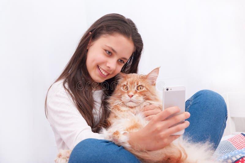 Flickan gör selfie med katten arkivfoto
