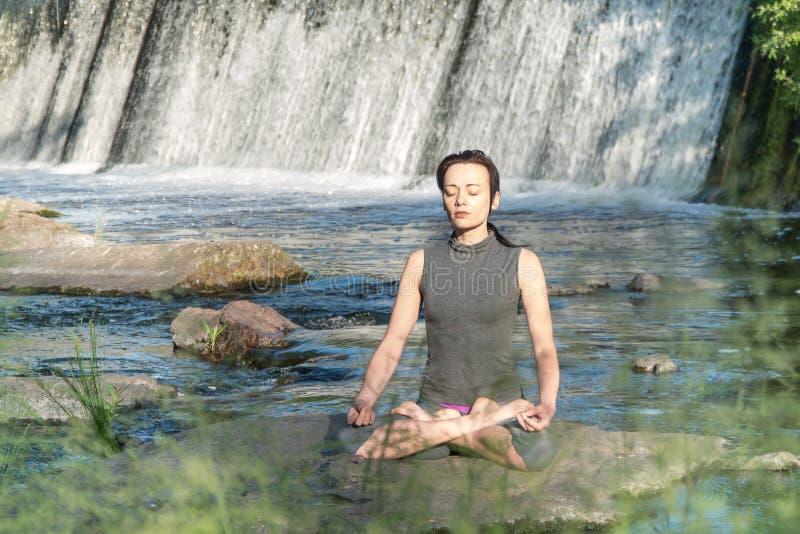 Flickan gör yoga i bakgrunden av en vattenfall arkivbild