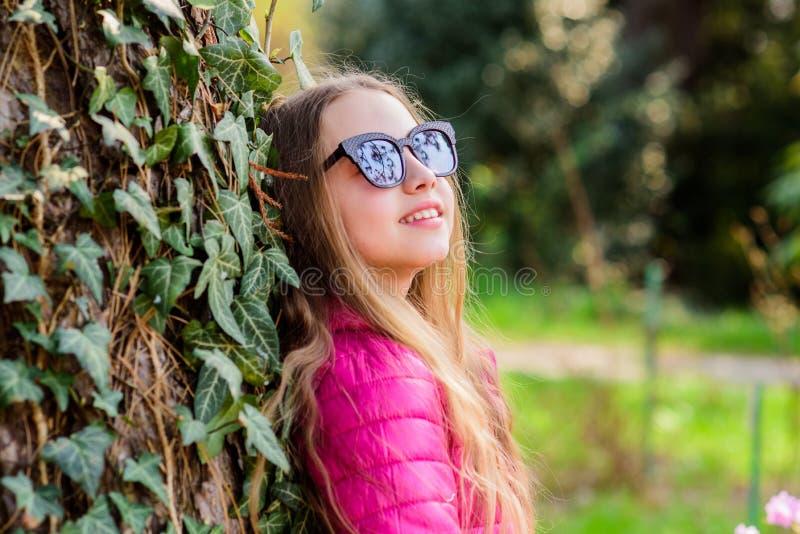 Flickan g?r i botanisk tr?dg?rd Tycka om naturen i tr?dg?rd Fridsam milj?tr?dg?rd Gulligt utsmyckat barn f?r unge att spendera ti arkivfoton