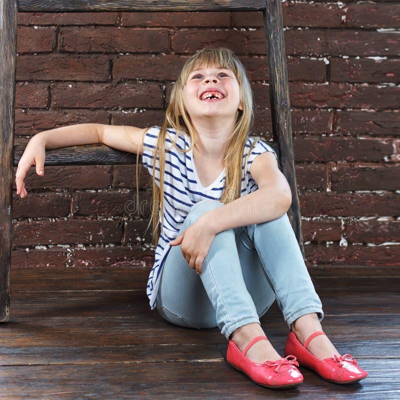 Flickan 6 gamla år i jeans och en väst sitter royaltyfri bild