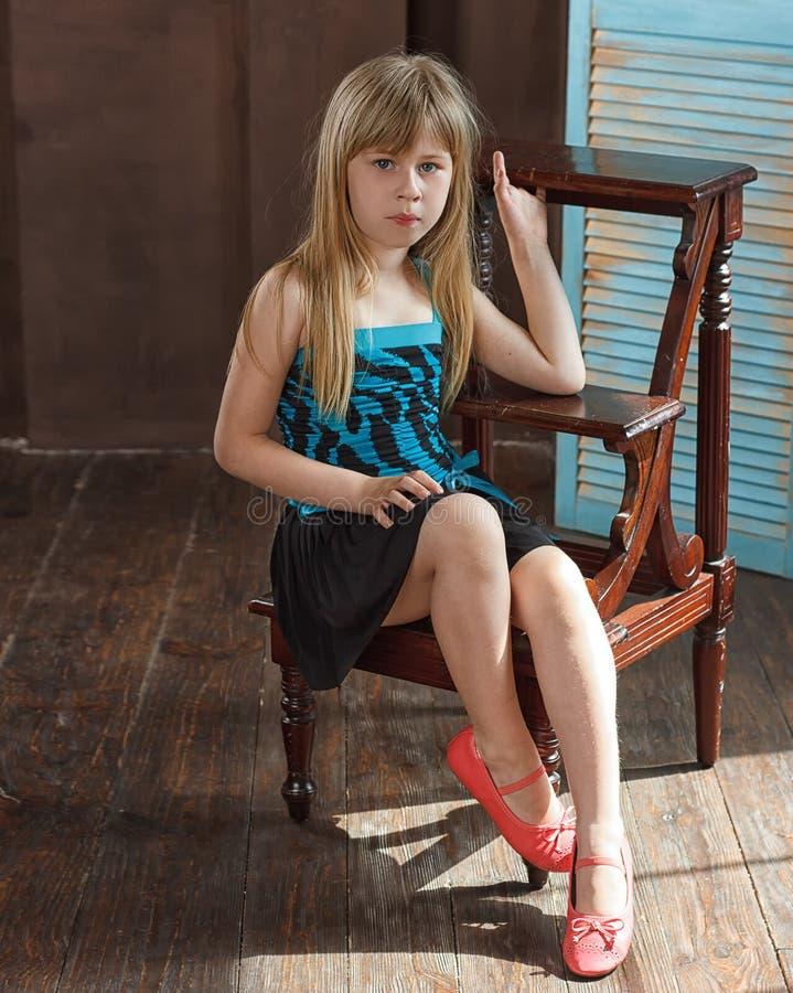 Flickan 6 gamla år i klänning sitter på en stol royaltyfri bild
