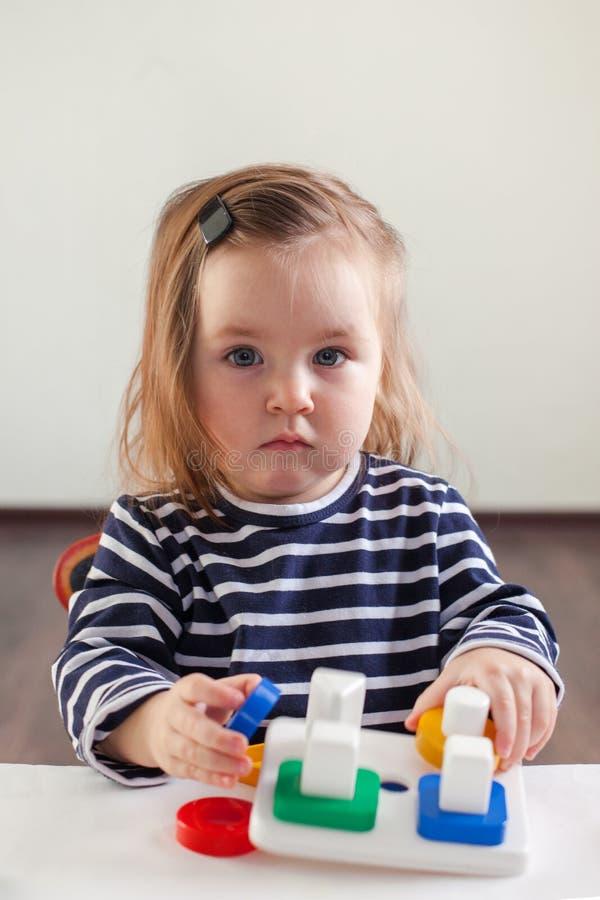 Flickan 1,5 gamla år med långt hår i en randig klänning sitter på tabellen och spelar med en framkallande leksak, den Montessori  arkivfoton