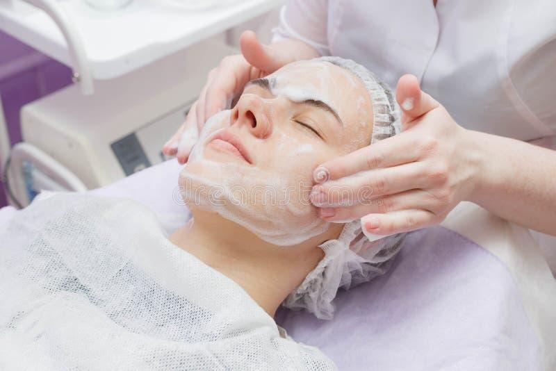 Flickan ges med en rengörande service för ultraljudhud i skönhetsalongen royaltyfria bilder