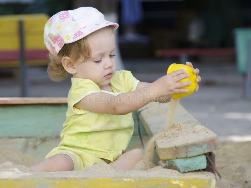 Flickan häller sand i en sandlåda royaltyfri fotografi