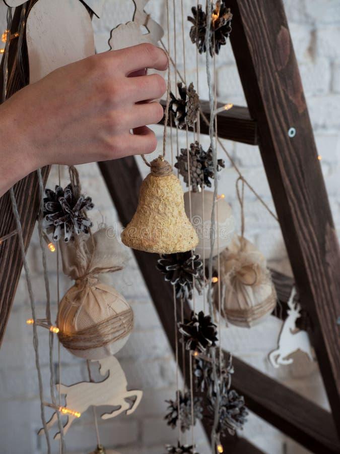 Flickan hänger hemlagade leksaker på en trätrappuppgång fotografering för bildbyråer
